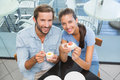 Young happy smiling couple eating cake while looking at the camera in cafe Stock Images