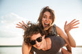 Young happy smiling couple in love piggyback at the beach Royalty Free Stock Photo