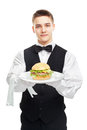 Young happy smiling waiter holding hamburger on plate Royalty Free Stock Photo