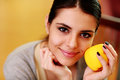 Young happy smiling woman holding yellow apple at home Stock Images