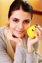 Young happy smiling woman holding yellow apple at home Royalty Free Stock Images