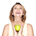 Young happy smiling woman holds green apple and looking up isolated on white Royalty Free Stock Photography