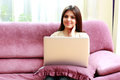 Young happy smiling woman sitting on the sofa with laptop at home Royalty Free Stock Image