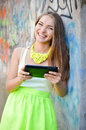 Young happy smiling woman working on pda tablet pc stylish beautiful outdoors Royalty Free Stock Image
