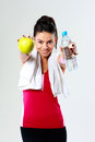 Young happy sport woman with apple and bottle of water on gray background Stock Photos