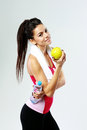 Young happy sport woman with apple and bottle of water on gray background Royalty Free Stock Image