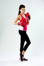 Young happy sports woman standing with boxing gloves on gray background Royalty Free Stock Image