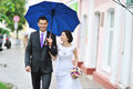Young happy wedding couple walking by the rain in an old town Royalty Free Stock Photo