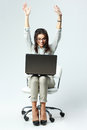 Young happy woman with arms up sitting on the chair with laptop Royalty Free Stock Photo