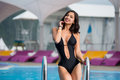 Young happy woman in the black swimsuit with shapely body near the swimming pool at the resort Royalty Free Stock Photo