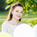 Young happy woman with bunch of balloons in park Royalty Free Stock Photo