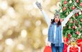 Young happy woman celebrating christmas over golden tree background Stock Photos