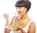 Young happy woman eating salad isolated on white Royalty Free Stock Photography