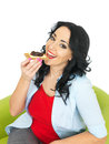 Young happy woman eating a wholegrain cracker with cheese and pickle healthy long black curly hair hispanic or european features Royalty Free Stock Images