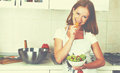Young happy woman eats vegetable salad on kitchen vegetarian Royalty Free Stock Photography