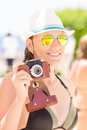 Young happy woman having fun with old camera in black bikini photo at the summer beach holidays Royalty Free Stock Images
