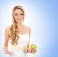 A young and happy woman measuring an apple Stock Photo