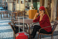Young happy woman with a red suitcase talking on the mobile phone at a sidewalk cafe.