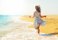Young happy woman running beach back to camera Stock Images