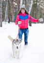 Young happy woman running with her dog in winter forest Stock Photos