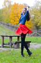 Young happy woman in short red skirt spinning around pretty outdoors on autumn day outdoors background smiling looking at camera Stock Photos