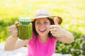 Young happy woman showing thumbs up with green smoothies at a picnic. Healthy food, detox and diet concept Royalty Free Stock Photo