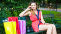 Young happy woman sitting on a bench with colorful shopping bags and mobile phone. Royalty Free Stock Photo