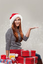 Young happy woman sitting next to christmas gifts wearing a santa hat with the hand in a holding object position Stock Photos