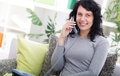 Young happy woman sitting on the sofa at home while talking on p phone Royalty Free Stock Photos
