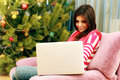Young happy woman sitting on the sofa and looking on the laptop at home Royalty Free Stock Image
