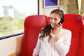 Young happy woman sitting in train talking on smart phone Royalty Free Stock Photo