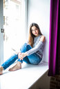 Young happy woman sitting on a window-sill at home and looking outside Royalty Free Stock Photo