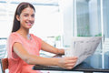 Young happy woman smiling at the camera while holding the newspaper Royalty Free Stock Photo