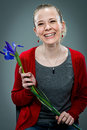 Young happy woman smiling violet flower over grey background Stock Photos