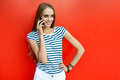 Young happy woman talking on mobile phone near red wall Royalty Free Stock Images