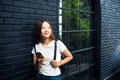 Young happy woman in white tshirt and blue jeans standing lnear Royalty Free Stock Photo