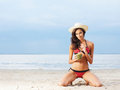 Young healthy beautiful and sexy woman in a white hat drinking an exotic cocktail the image is taken on the beach Royalty Free Stock Image