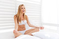 Young healthy beautiful woman sitting in lotus position in bed Royalty Free Stock Photo
