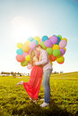 Young healthy beauty pregnant woman with her husband and balloon beautiful women balloons outdoors a men girl a tummy on the grass Royalty Free Stock Images