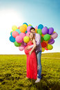 Young healthy beauty pregnant woman with her husband and balloon beautiful women balloons outdoors a men girl a tummy on the grass Stock Images