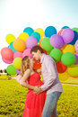 Young healthy beauty pregnant woman with her husband and balloon beautiful women balloons outdoors a men girl a tummy on the grass Royalty Free Stock Photo