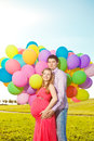 Young healthy beauty pregnant woman with her husband and balloon beautiful women balloons outdoors a men girl a tummy on the grass Royalty Free Stock Photography