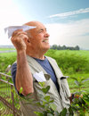 Young at heart smiling elderly man sending flying paper airplanes Royalty Free Stock Photos