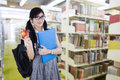 Young high school student in library attractive female standing the while holding a red apple and folder Stock Photos