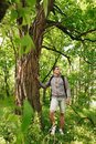 Young hiker man with backpack walking in summer forest. Travelling male standing near a big tree