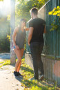 Young hiphop couple in a urban environment styled standing next to fence during sunset r Royalty Free Stock Photography
