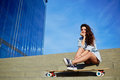 Young hipster girl posing at beautiful sunset light looking away charming sits on the steps with big skyscraper on background Stock Photos