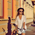 Young hipster girl on a retro bicycle. Outdoor fashion portrait Royalty Free Stock Photo