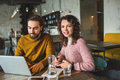 Young hipster male and female working laptop together in cafe Royalty Free Stock Photo
