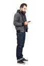 Young hipster wearing jacket over hooded sweatshirt typing on mobile phone full body length portrait isolated white studio Royalty Free Stock Photo